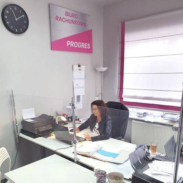 Kobieta siedzi przy biurku zaszybką
