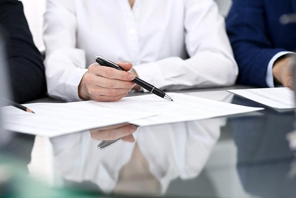 Mężczyzna siedzący przy stole wskazuje dane nakartce